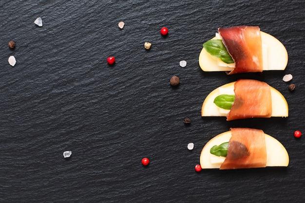 Apéritif de noël, bœuf séché aux pommes, au brie et au brie séché sur une plaque d'ardoise noire Photo Premium