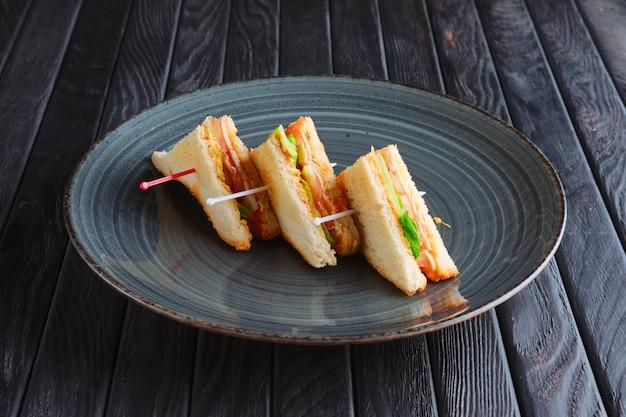 Apéritif à la réception. trois mini club sandwich sur assiette Photo Premium