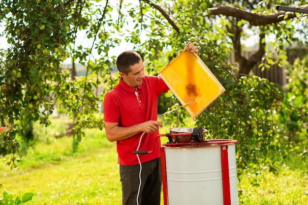 Apiculteur coupant la cire du cadre en nid d'abeille avec un couteau électrique spécial Photo Premium