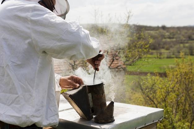 Apiculteur extrayant du miel Photo gratuit
