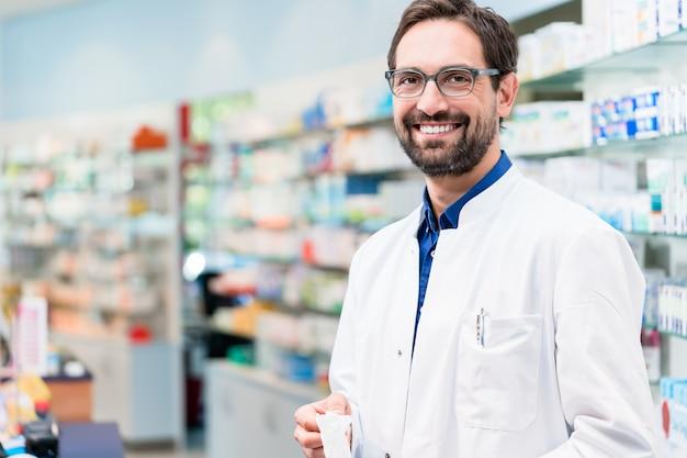 Apothicaire en pharmacie debout sur une étagère avec des médicaments Photo Premium