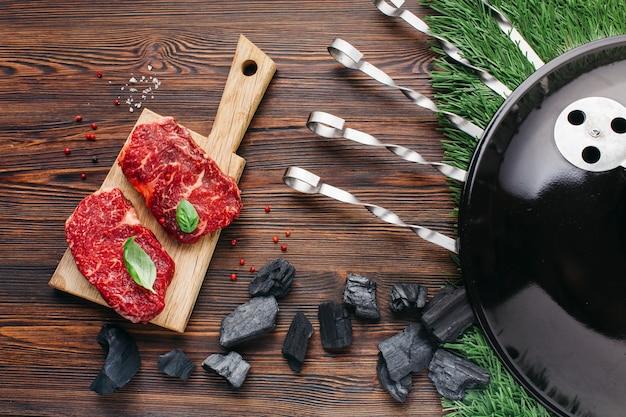 Appareil De Barbecue Avec Steak Cru Sur Une Planche à Découper Sur Un Bureau En Bois Photo gratuit