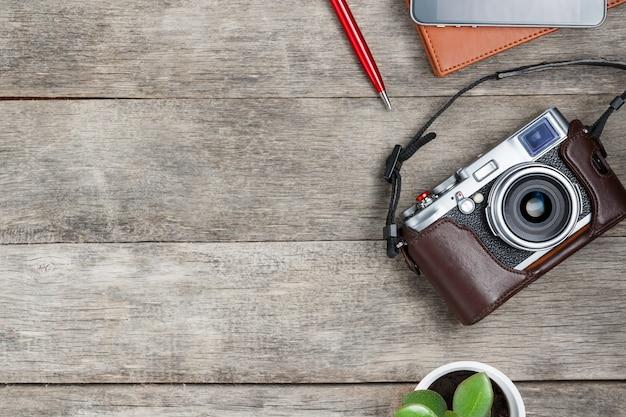 Appareil photo classique, avec un bloc-notes marron, un stylo rouge, un téléphone et une croissance verte. liste de concept pour un photographe de voyage Photo Premium