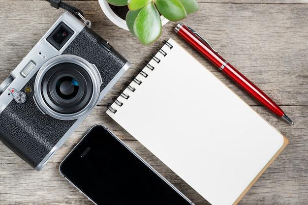 Appareil photo classique avec page vierge du bloc-notes et stylo rouge sur un bureau vintage en bois gris avec téléphone. Photo Premium