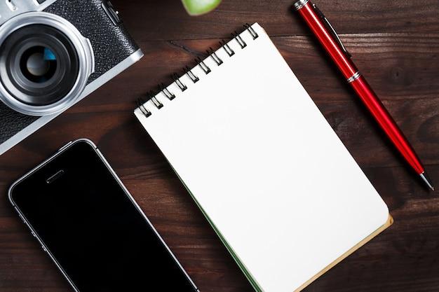 Appareil photo classique avec page vierge du bloc-notes et stylo rouge sur une table en bois marron foncé, table vintage avec téléphone et fleur verte Photo Premium