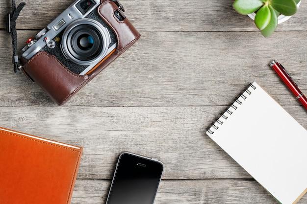 Appareil photo classique avec une page vierge du bloc-notes et un stylo rouge sur une table vintage en bois grise avec téléphone et fleur verte. cahier marron. Photo Premium