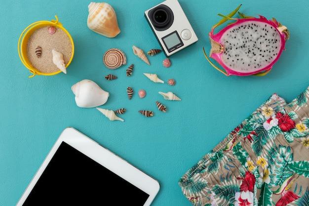 Appareil photo, coquillage, sable, pantalon de plage, fruit du dragon et smartphone sur bleu Photo Premium