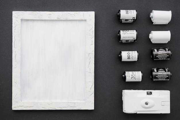 Appareil photo et film près du cadre blanc Photo gratuit