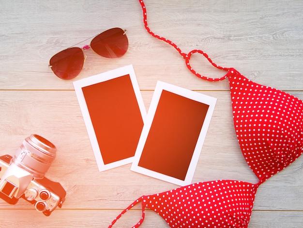 Appareil photo, lunettes, photos vierges, maillot de bain sur un fond en bois. Photo Premium