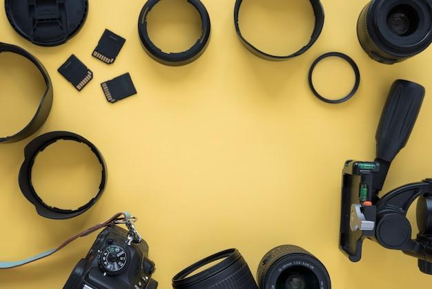 Appareil photo moderne dslr professionnel avec accessoires pour appareils photo sur fond jaune Photo gratuit