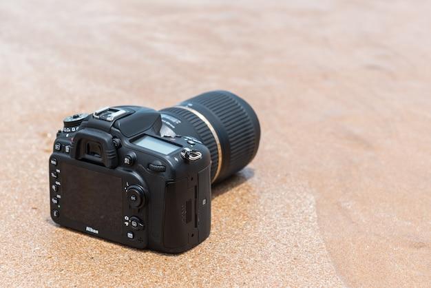 Appareil photo reflex numérique sur la plage mouillée par la vague de mer Photo Premium