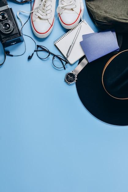 Appareil photo rétro, chapeau, sac à dos, lunettes, horloge, stylo, passeport, chaussures et bloc-notes. Photo Premium