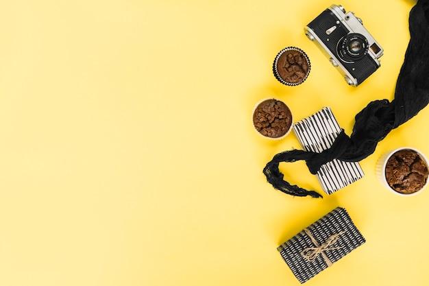 Appareil photo rétro et cupcakes près de cadeaux Photo gratuit