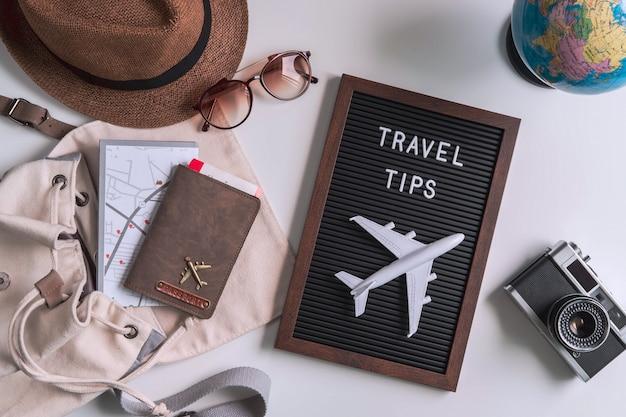 Appareil photo rétro avec jouet avion, carte et passeport sur fond blanc Photo Premium
