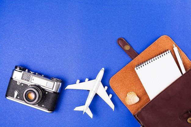 Appareil photo rétro près d'un avion jouet et étui avec bloc-notes Photo gratuit