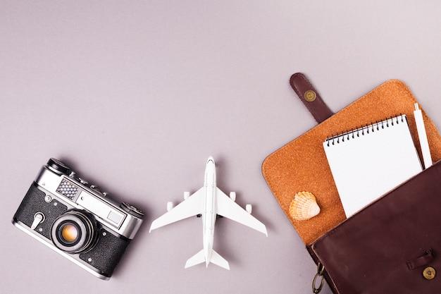 Appareil photo rétro près d'un avion jouet et étui avec ordinateur portable Photo gratuit