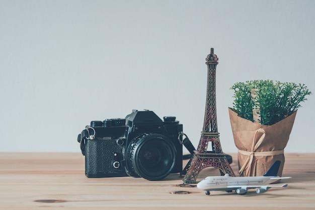 Appareil photo, simulateur de tour eiffel, simulateur d'avion, posé sur un plancher en bois concepts de planification de voyage Photo Premium