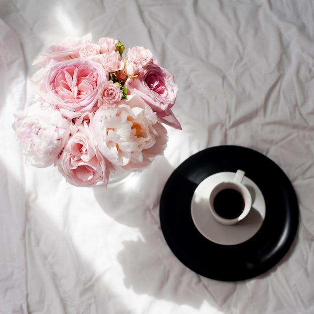 Appartement de beauté poser avec café et bouquet de fleurs roses et pions Photo Premium