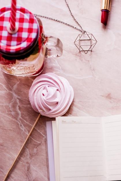 Appartement de beauté poser avec un journal intime, accessoires, rouge à lèvres, merengue et pot avec de l'eau sur un fond de marbre Photo Premium