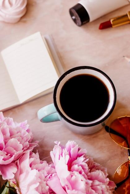Appartement de beauté poser avec un journal, une tasse de café, des accessoires et des pivoines sur un fond de marbre Photo Premium