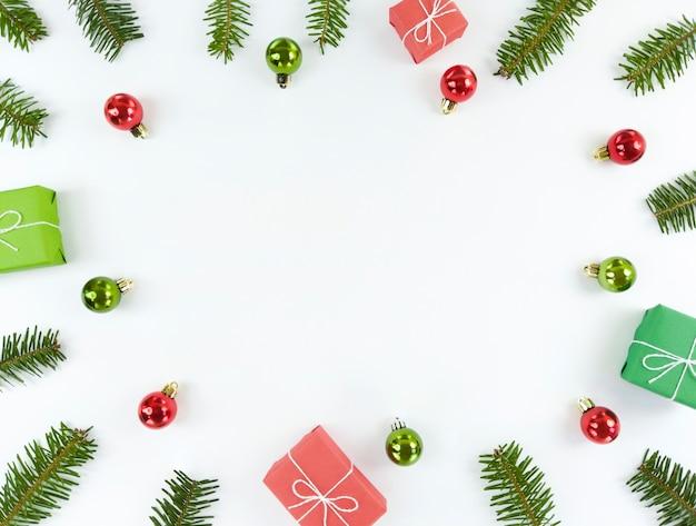 Appartement De Noël Avec Espace Copie Au Milieu. Branches D'arbres, Boules Vertes Et Rouges, Coffrets Cadeaux Sur Fond Blanc. Photo Premium