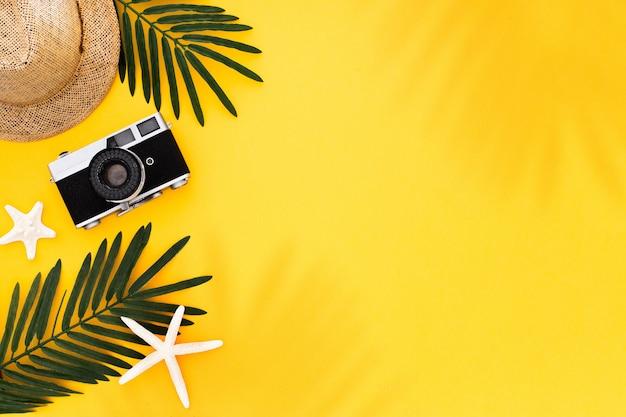 Appartement posé avec accessoires de voyage: feuille de palmier tropical, appareil photo rétro, chapeau de soleil, étoile de mer sur fond jaune Photo gratuit