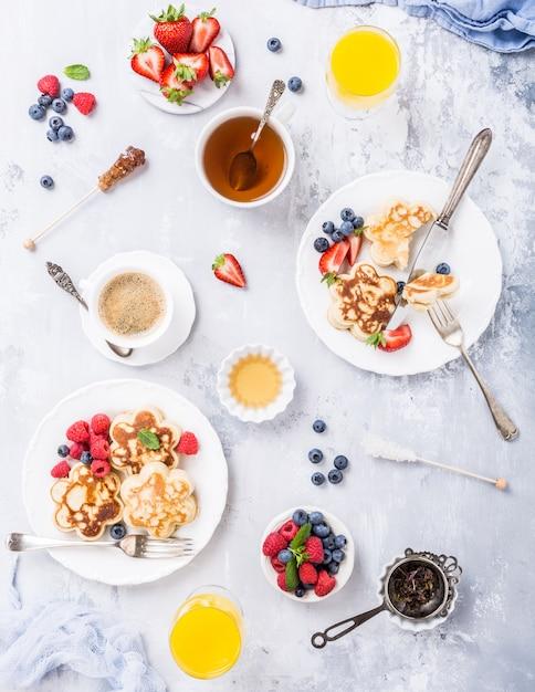 Appartement poser avec petit déjeuner avec des crêpes scotch sous forme de fleurs, de baies et de miel sur une table en bois clair. Photo Premium