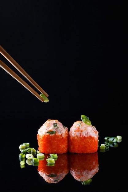 Appétissant rouleau de sushi cuit au four avec poisson, oignons verts et baguettes sur fond noir Photo Premium