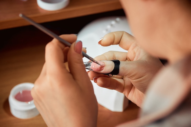 Appliquer le vernis à ongles en gel, la femme faisant la manucure. Photo Premium