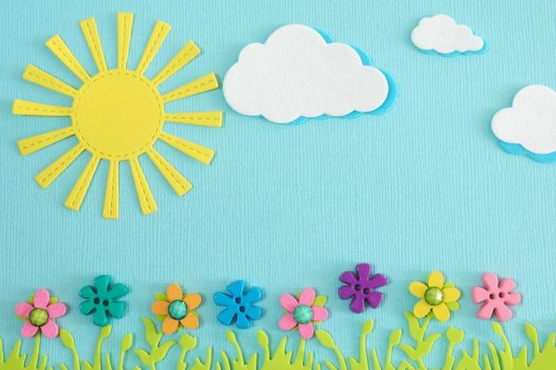 Appliques soleil jaune, nuages, herbe verte luxuriante et fleurs multicolores lumineuses sur fond bleu. Photo Premium