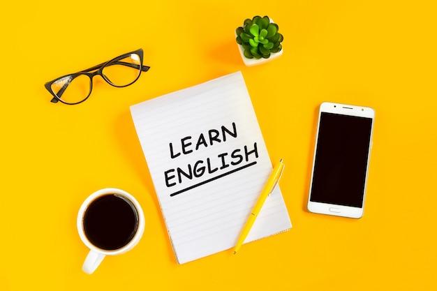 Apprendre l'anglais concept. bloc-notes, téléphone portable, tasse de café, lunettes Photo Premium