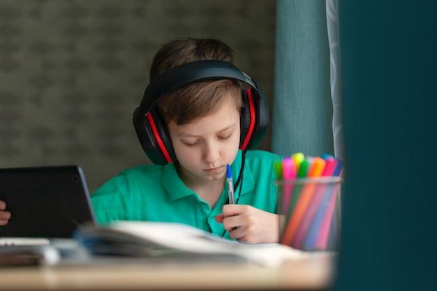 Apprentissage à Distance Enfant écrit Ses Devoirs Avec Tablette Numérique. L'éducation En Ligne Concept. Photo Premium