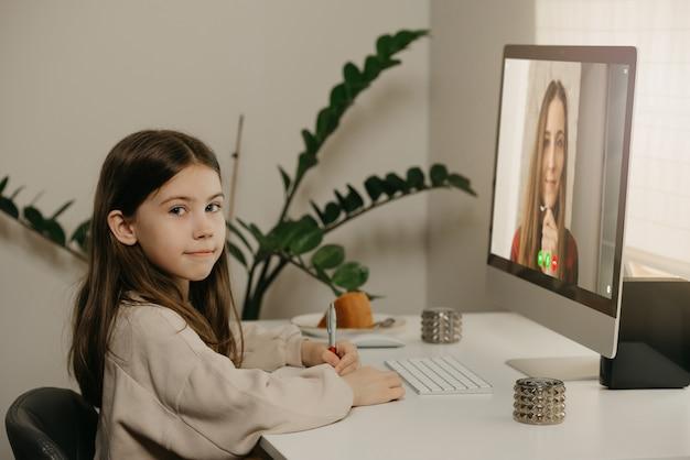 Apprentissage à Distance. Une Jeune Fille Aux Cheveux Longs étudie à Distance à Partir De Son Professeur En Ligne. Une Jolie Enfant Apprend Une Leçon à L'aide D'un Ordinateur De Bureau à La Maison. éducation à Domicile. Photo Premium
