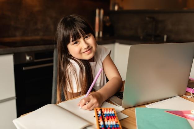 Apprentissage En Ligne, écolière étudie Les Devoirs Pendant Sa Leçon En Ligne à La Maison Photo Premium