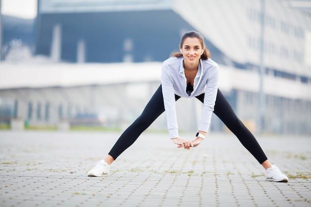 Aptitude. femme faisant de l'exercice dans la rue Photo Premium
