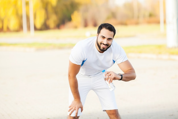 Aptitude. homme fatigué coureur reste après avoir couru sur la ville stree Photo Premium