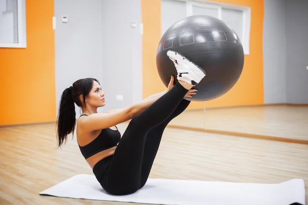 Aptitude. jeune femme à l'entraînement avec ballon de fitness Photo Premium
