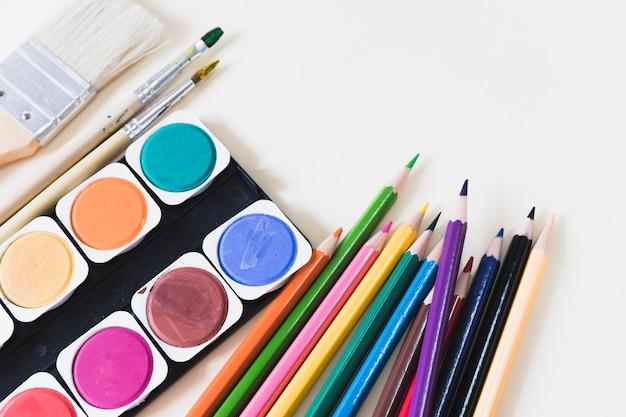 Aquarelle au milieu des crayons et des pinceaux Photo gratuit