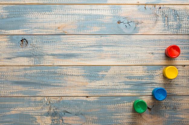 Aquarelle contenants disposés sur une vieille surface en bois Photo gratuit