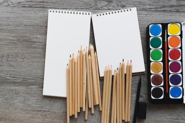 Aquarelle et crayons près des carnets de croquis Photo gratuit