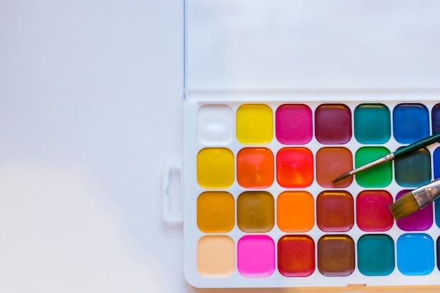 Aquarelle peintures et pinceaux sur fond blanc. cours de peinture. espace de copie Photo Premium