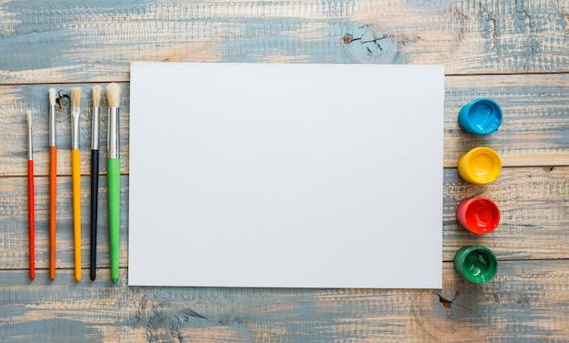 Aquarelle petits contenants et pinceaux avec une feuille blanche Photo gratuit