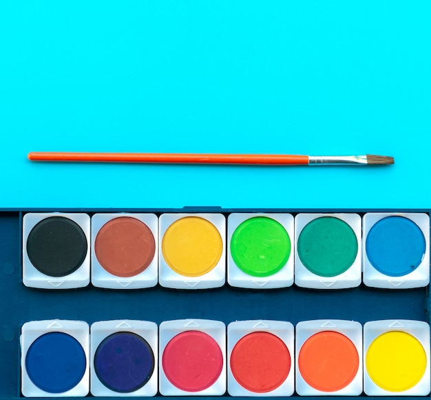 Aquarelle et pinceau posés sur la table de peinture Photo Premium