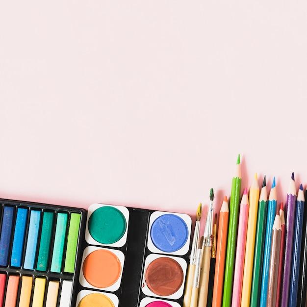 Aquarelle et pinceaux près des outils de dessin Photo gratuit