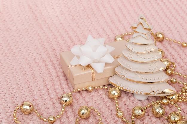 Arbre De Noël Décoratif, Boîte-cadeau Et Guirlande Or Sur Fond Tricoté Rose. Nouvel An Ou Noël. Photo Premium