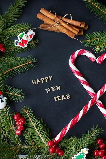 Arbre De Noël Avec Des Ornements Et Des Bonbons Sur Un Fond Noir. L'inscription Bonne Année Photo Premium