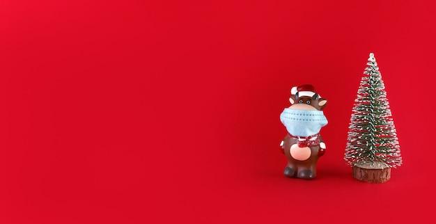 Arbre De Noël Et Statuette En Céramique De Boeuf En Masque Médical Sur Fond Rouge Avec Espace Copie. Symbole De La Nouvelle Année 2021. Photo Premium