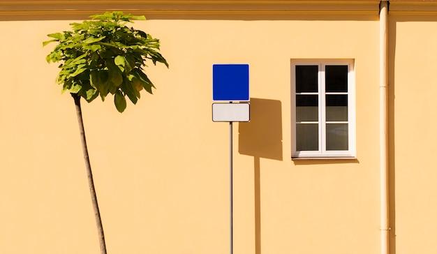 Un Arbre Et Un Panneau De Signalisation Sur Un Mur Jaune Photo Premium