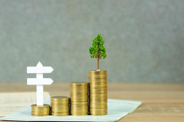Arbre qui pousse sur des tas de pièces d'or et livre de compte ou de crédit et panneau de bois blanc Photo Premium