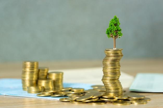 Arbre qui pousse sur des tas de pièces d'or et livre de compte ou panier Photo Premium